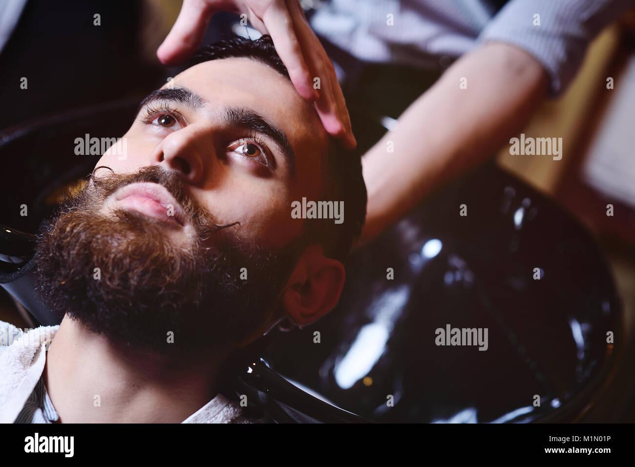 Coiffeur ou se lave la tête du client Photo Stock