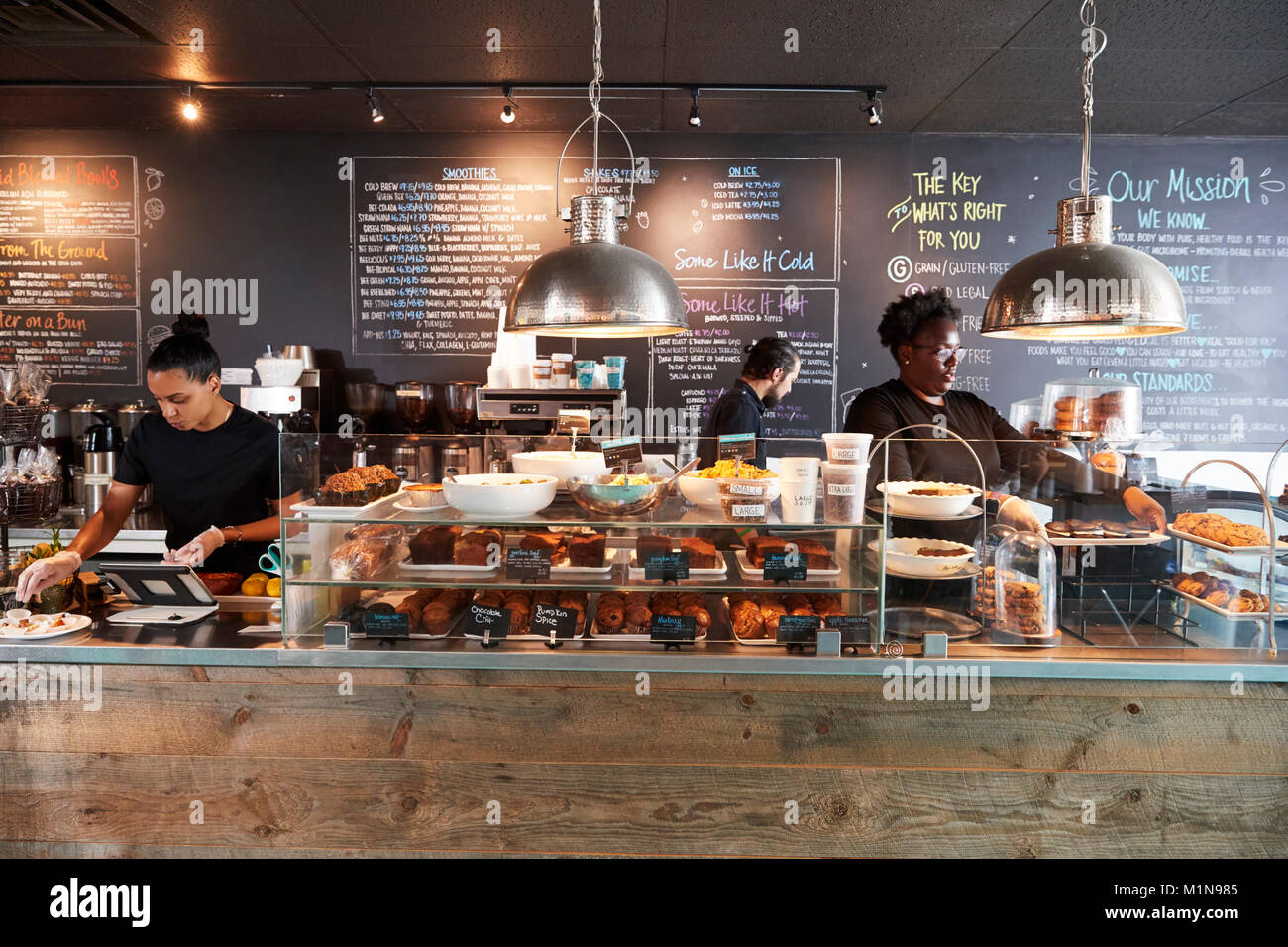 Le personnel travaillant dans les présentoirs de comptoir café occupé Photo Stock