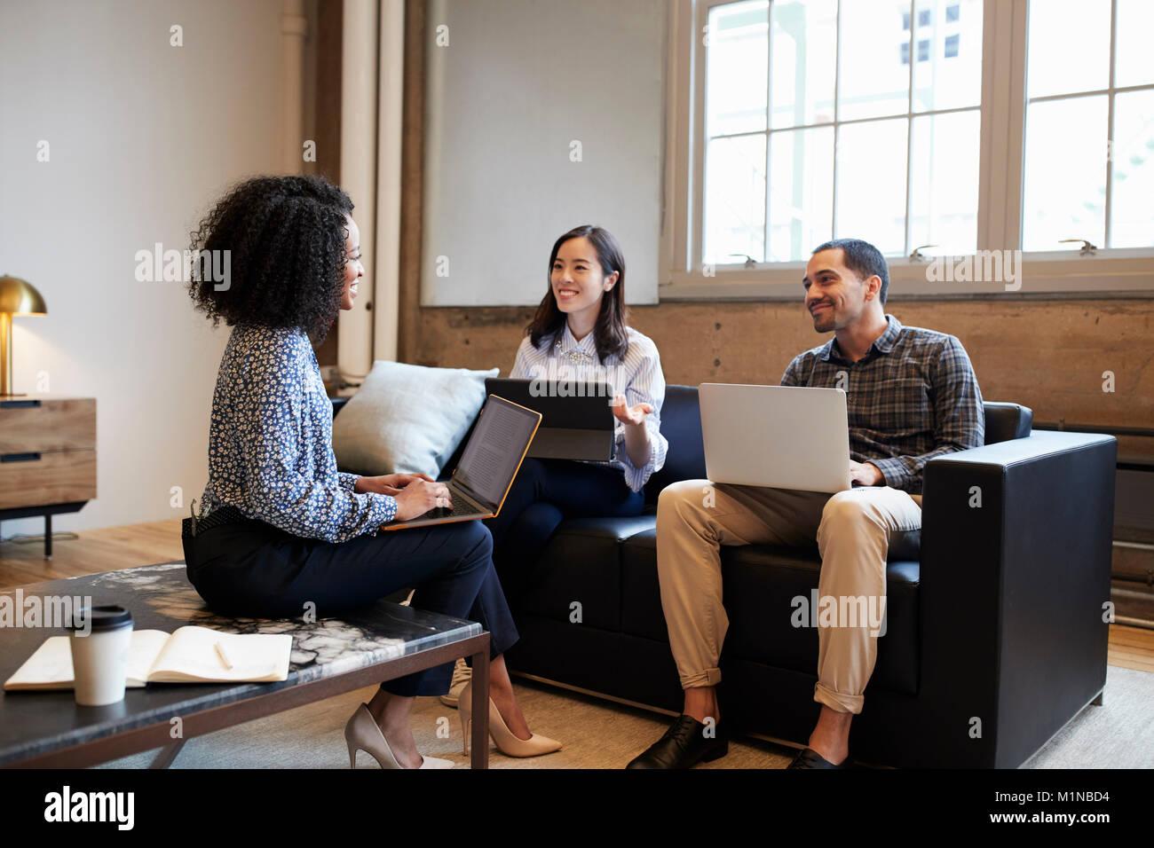 Des collègues de travail avec un ordinateur portable souriant lors d'une réunion décontractée Photo Stock