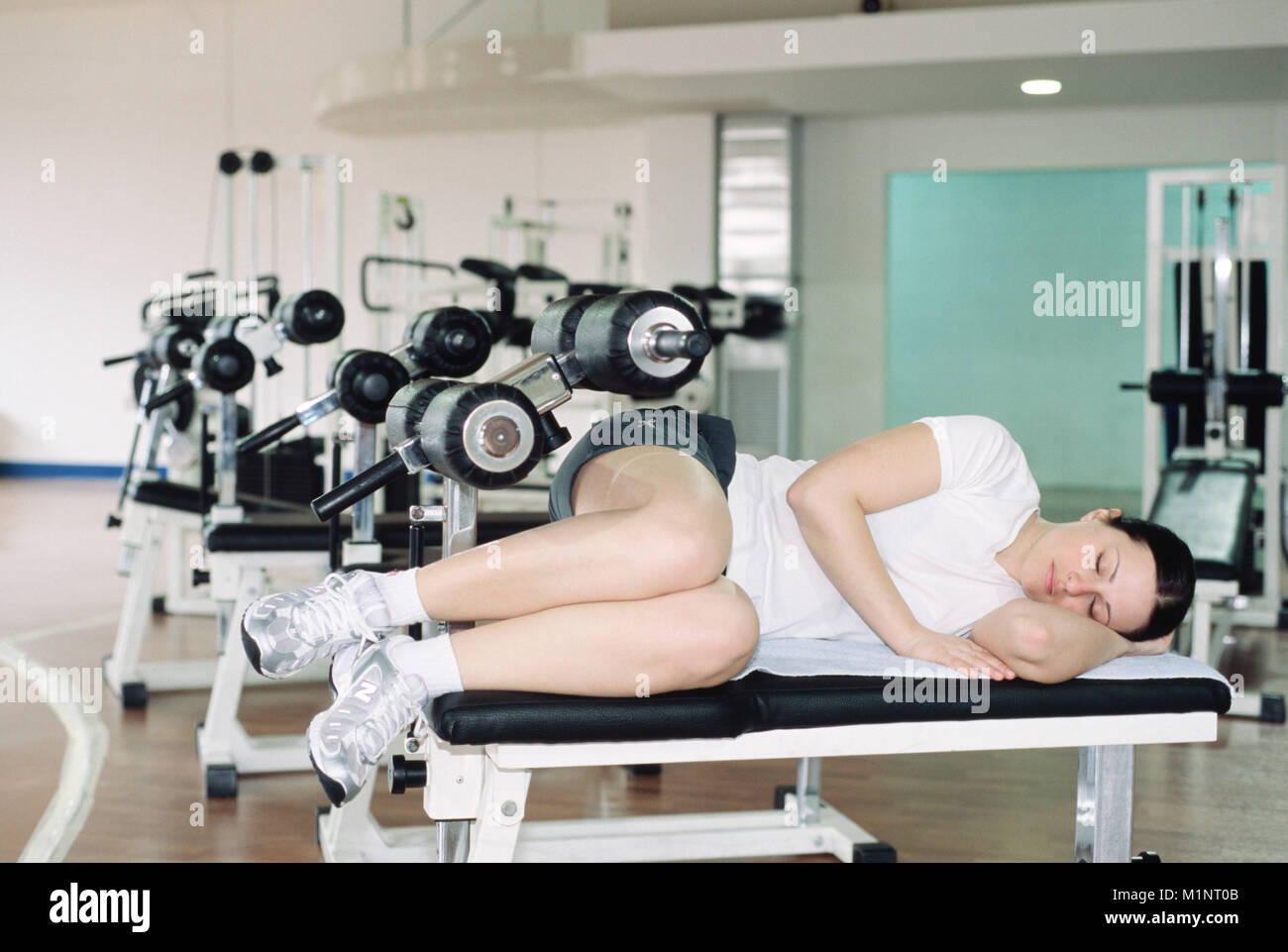Jeune femme dormir dans la salle de sport Photo Stock
