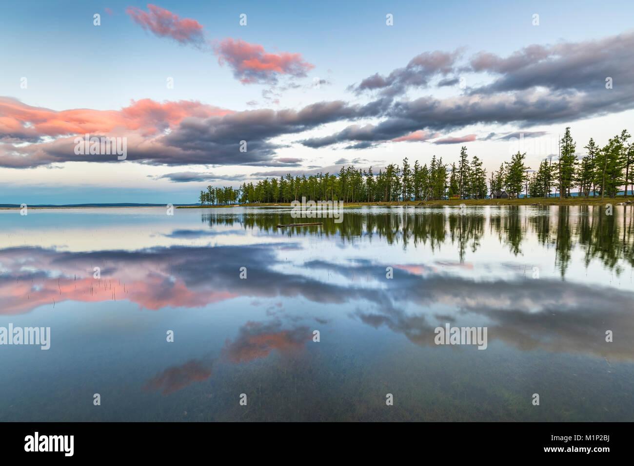 Sapins et les nuages reflétant sur la surface du lac Hovsgol au coucher du soleil, China, la Mongolie, l'Asie Photo Stock