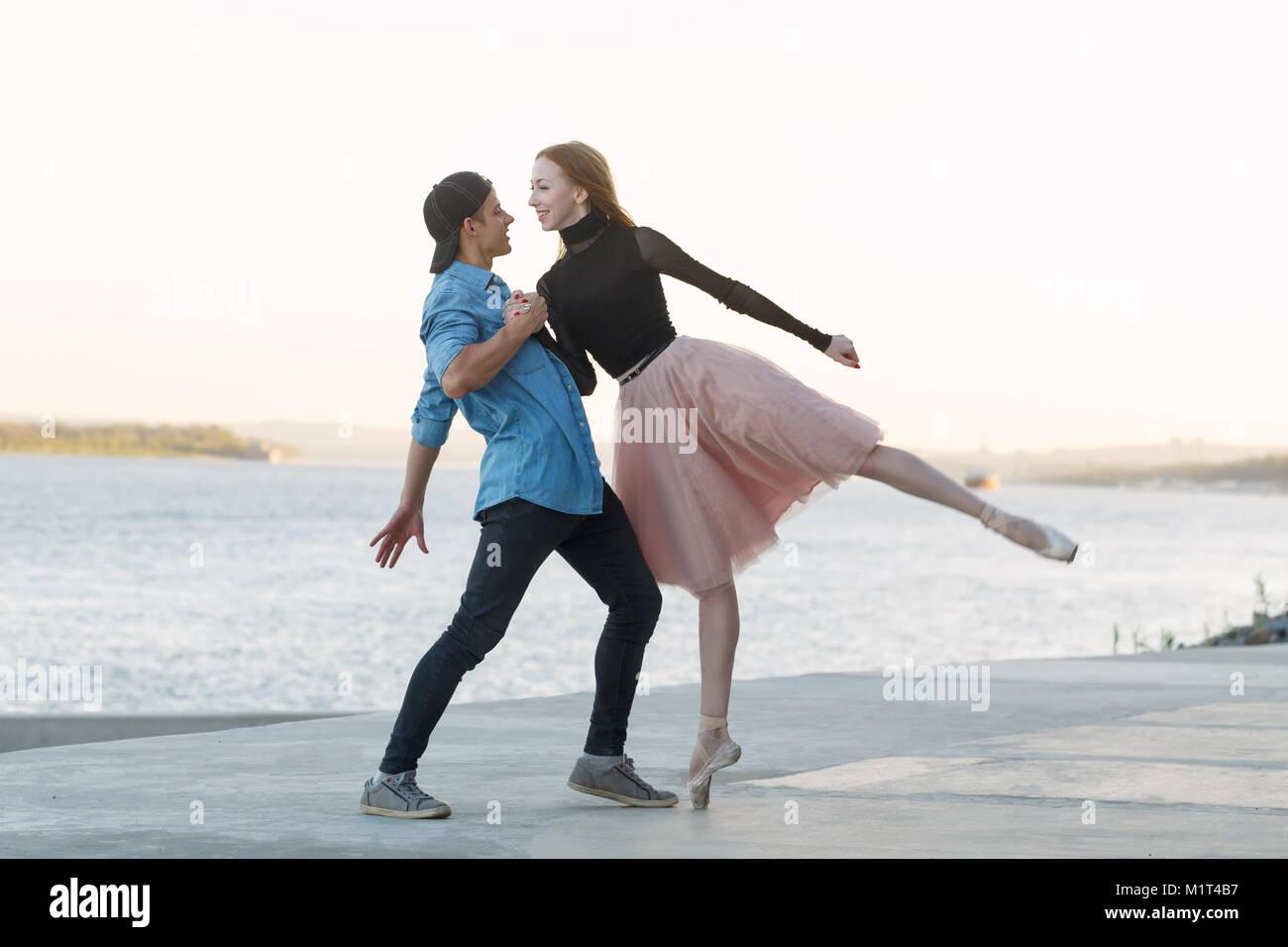 Une ballerine danse avec une danseuse moderne. Les amateurs de rencontres. Passion et amour de la danse. Il la tient Photo Stock