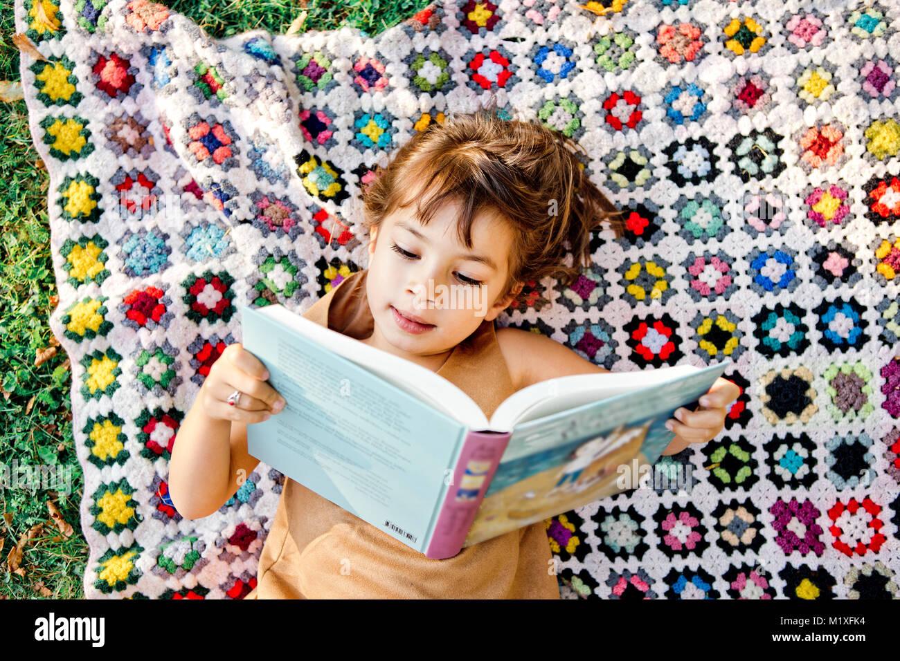 Girl reading on picnic blanket dans Friseboda, Suède Photo Stock