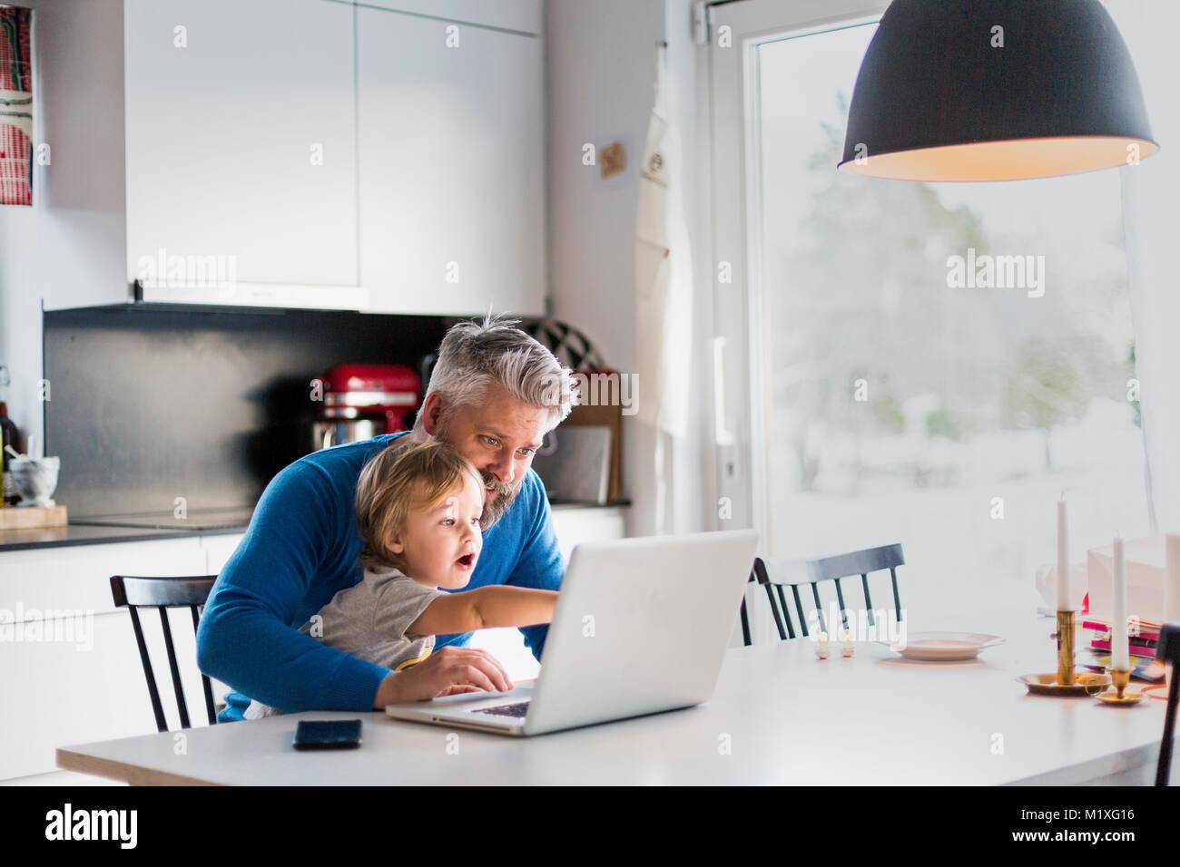 L'homme et l'enfant jouant avec un ordinateur portable dans la cuisine Photo Stock
