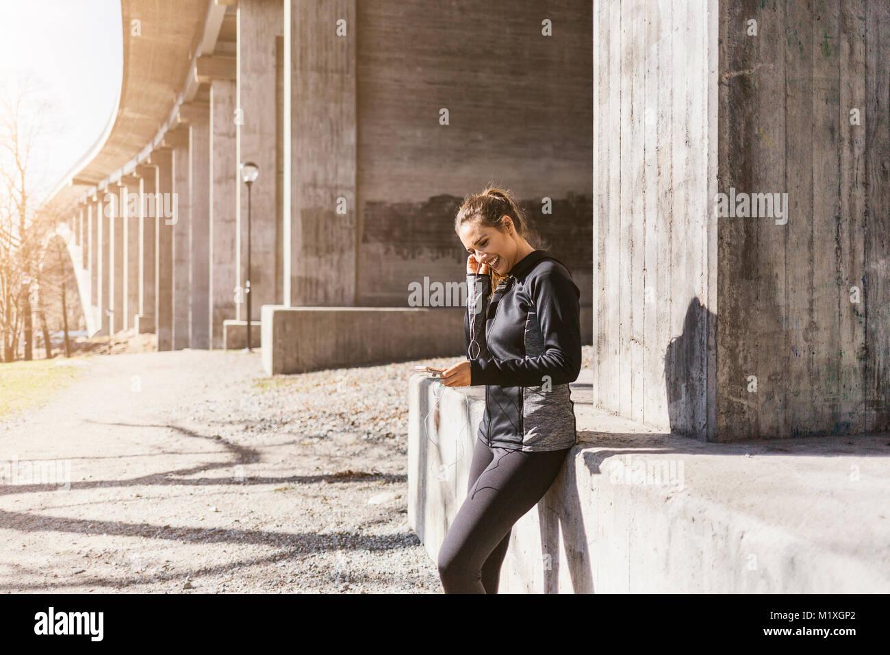 Jeune femme avec smart phone sur rue à Stockholm, Suède Photo Stock