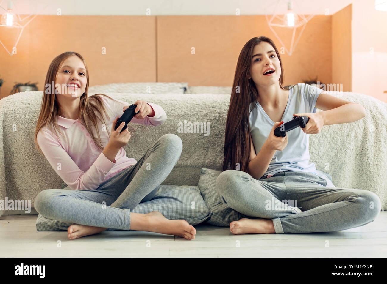 Deux sœurs adolescentes jouer jeu vidéo dans la chambre Photo Stock