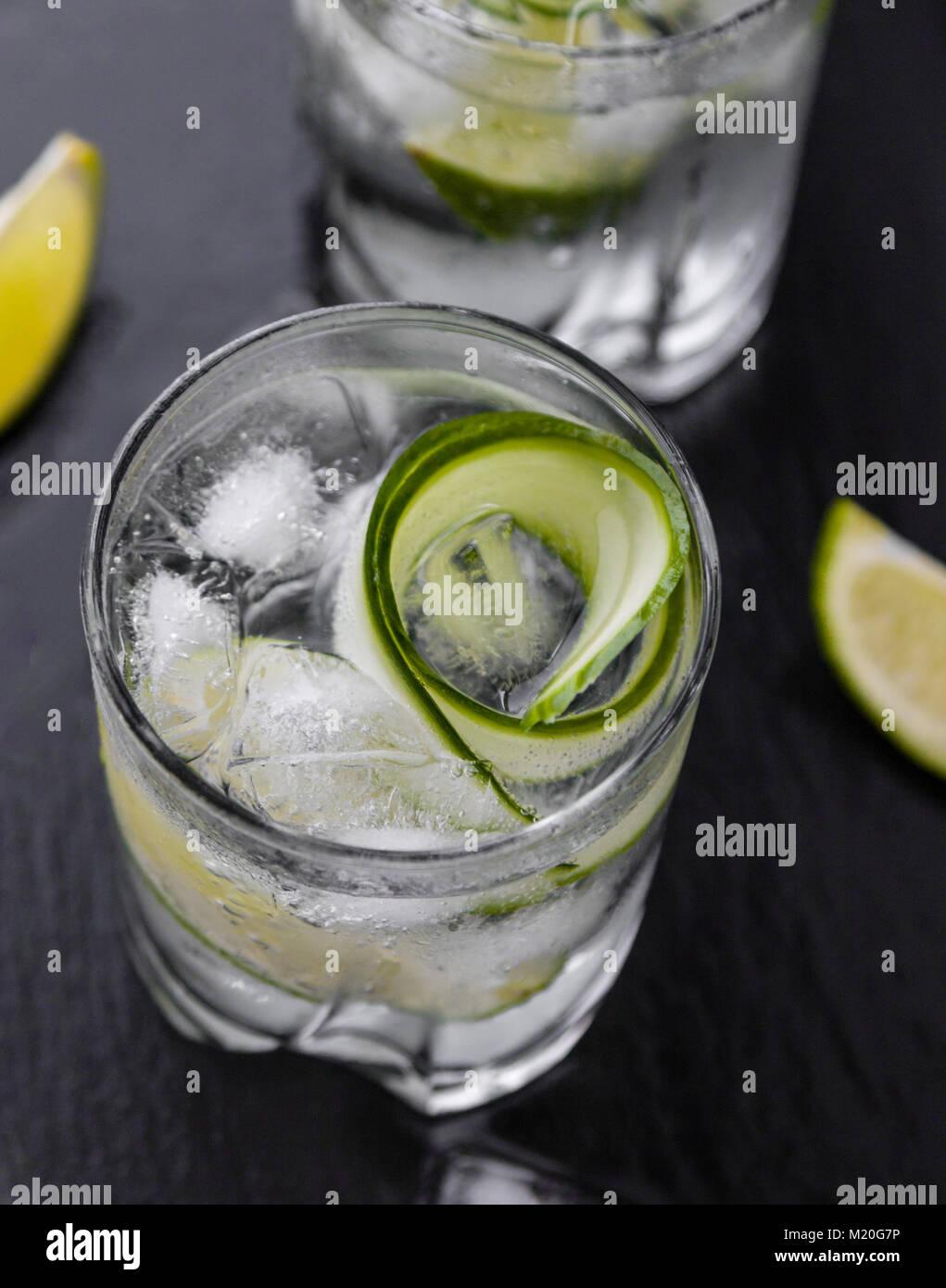Gin Tonic avec le concombre, citron vert et de la glace dans le verre Photo Stock