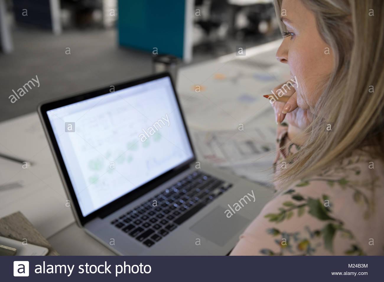 L'examen des plans de l'architecte numérique on laptop in office Photo Stock