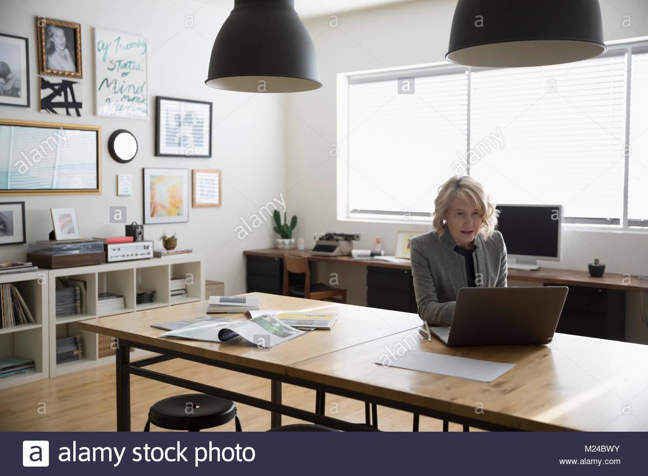 Entrepreneur spécialisé senior businesswoman working at laptop in office studio Photo Stock