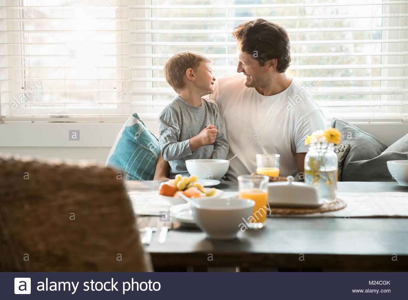 Heureux père et fils manger le petit déjeuner en coin petit-déjeuner Photo Stock