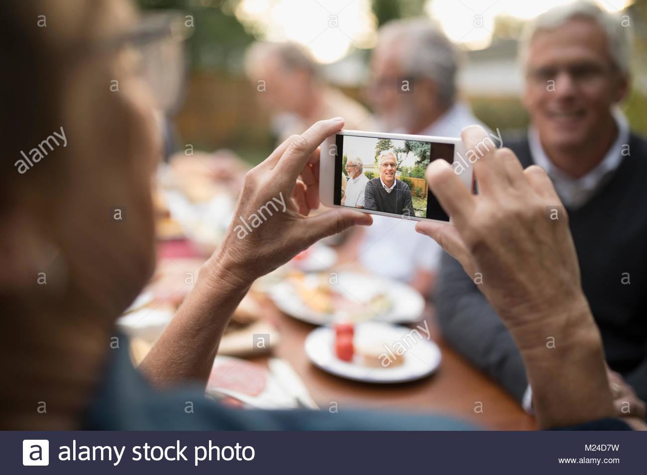Senior woman photographing mari avec téléphone appareil photo à table patio Photo Stock