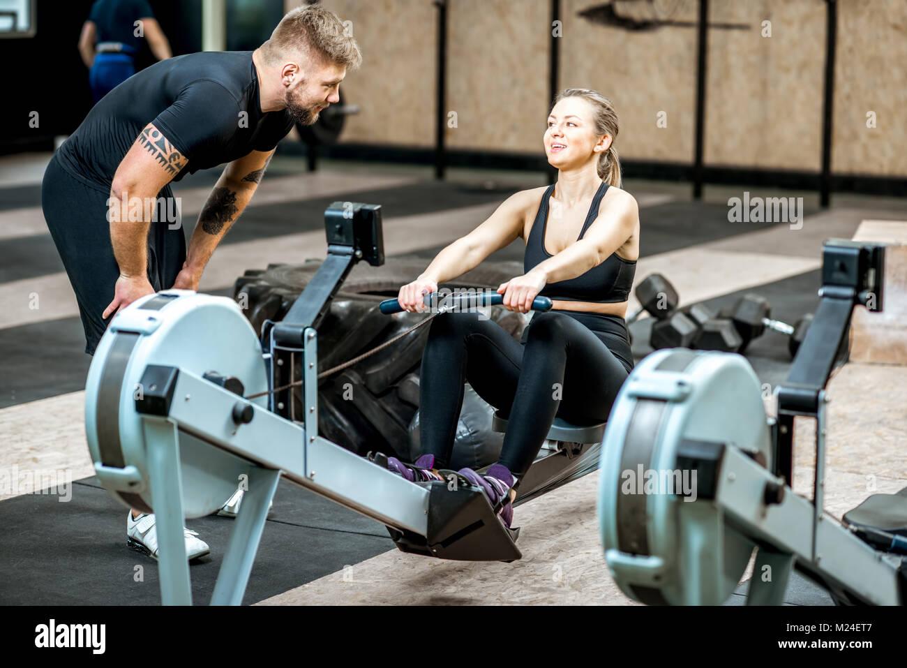 Formation de coach femme sur la machine d'exercice Photo Stock