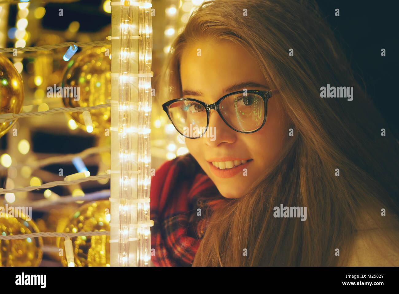 Une douce jeune fille hipster avec des lunettes et une écharpe promenades  au bord de la vitrine. Elle sourit. Portrait de nuit suivant pour les  guirlandes. 114280cd982