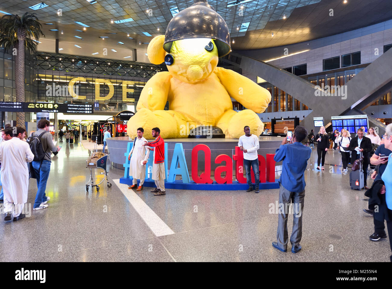 Qatar, Doha, Hamad Aéroport International. Dans la zone de transit à l'entrée principale, les visiteurs se réunissent autour de la lampe pour l'ours géant photos. Banque D'Images