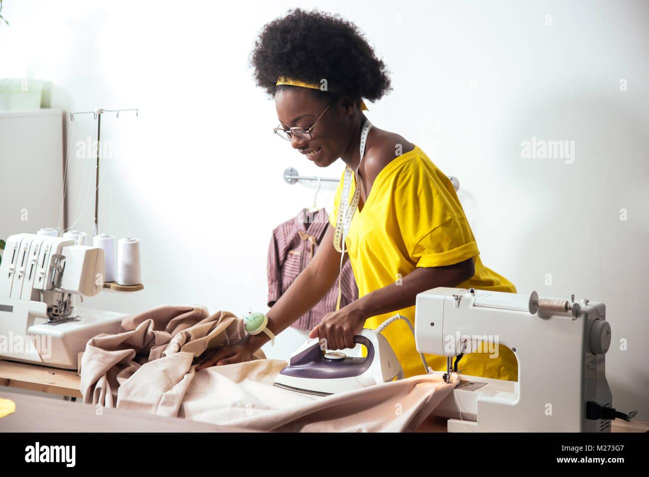 Femme africaine couturière chiffon repassage Photo Stock