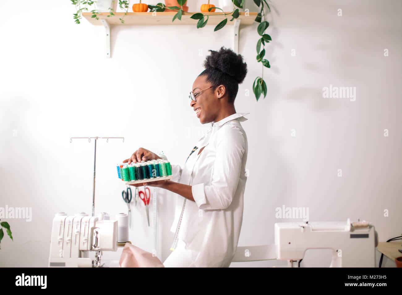 Couturière africaine holding bobines avec filetage Photo Stock