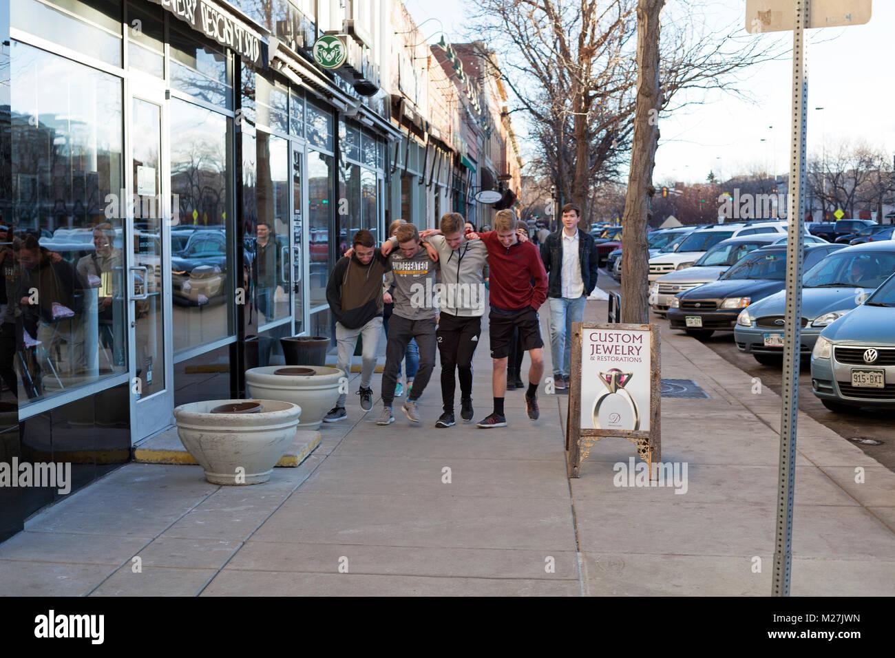 Un groupe d'amis se bloque les bras et éviter le trottoir à Fort Collins, Colorado, USA. Banque D'Images