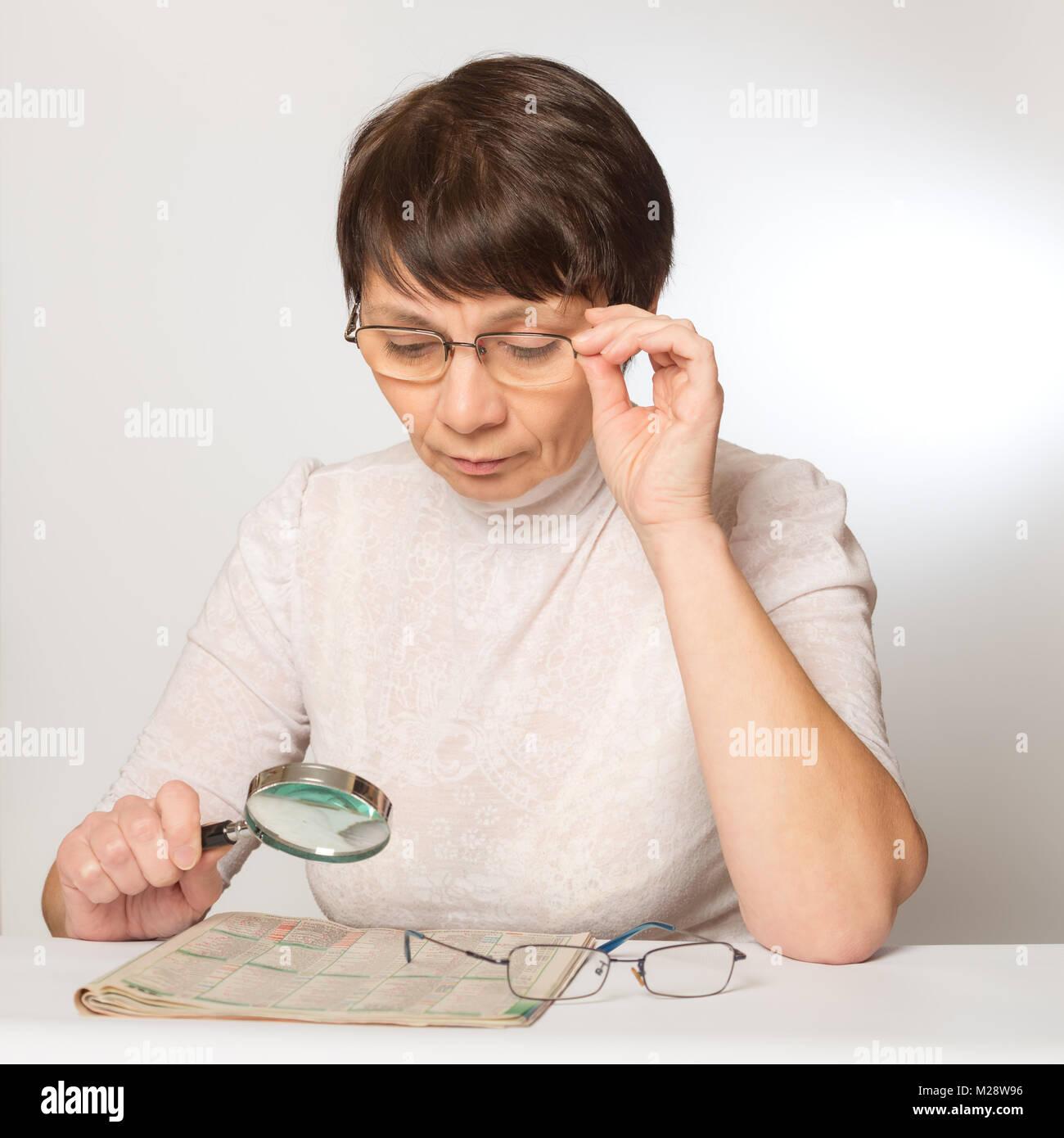 Des problèmes de vision. Femme avec des lunettes et une loupe lire un  journal Photo 9bd2c5d15335