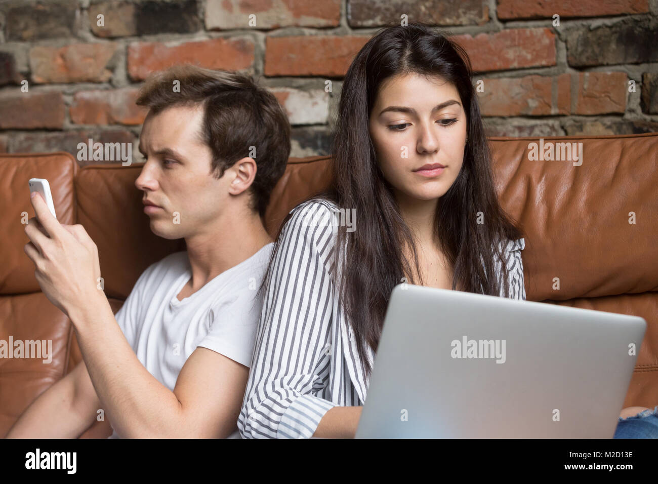 Young couple sitting on couch addicted obsédé par gadg moderne Photo Stock