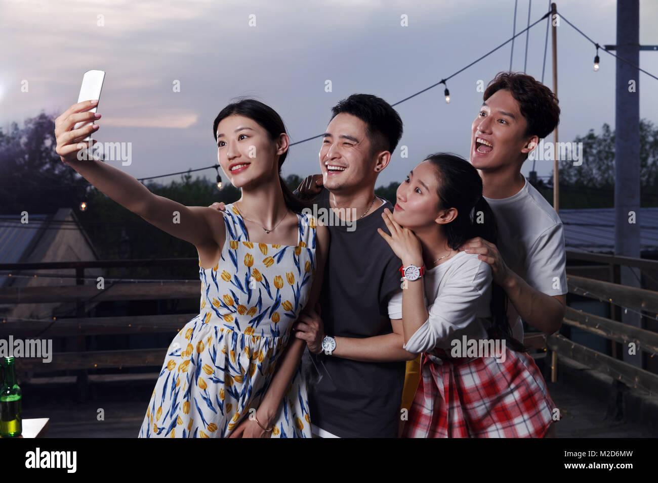 Les jeunes prennent des photos avec leurs téléphones portables Photo Stock
