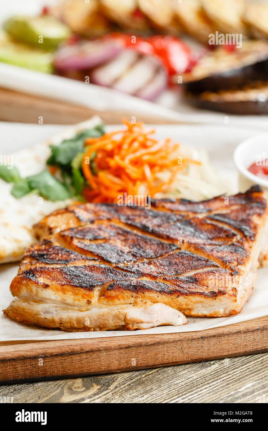Grill Steak de porc. Servir sur une planche en bois sur une table rustique. Restaurant Barbecue menu, une série de photos de différentes viandes Banque D'Images