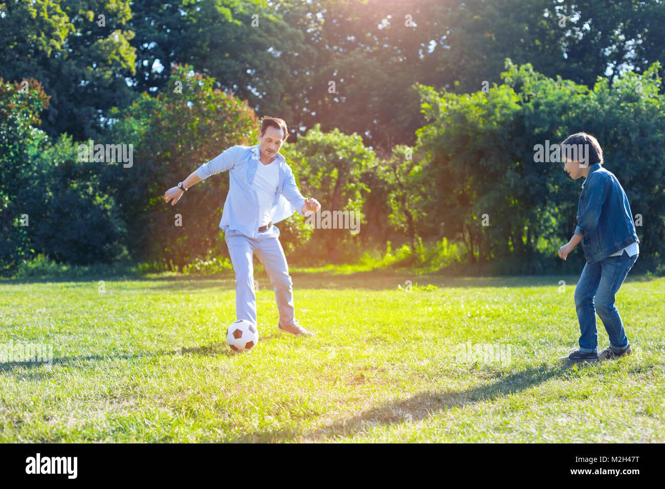 Joyeux père et fils jouent au football ensemble Photo Stock