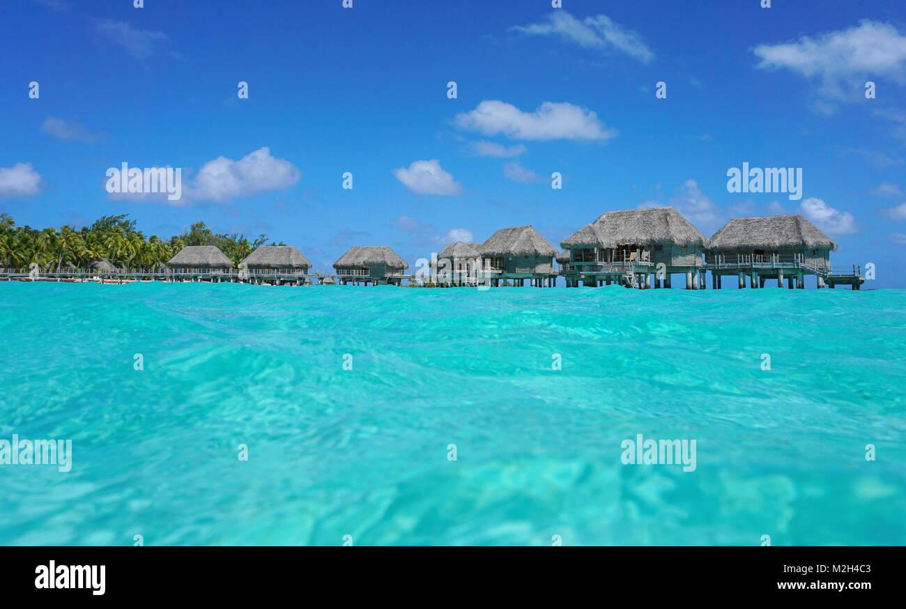 Bungalows sur pilotis au toit de chaume dans un lagon tropical, vu à partir de la surface de la mer, l'atoll Photo Stock