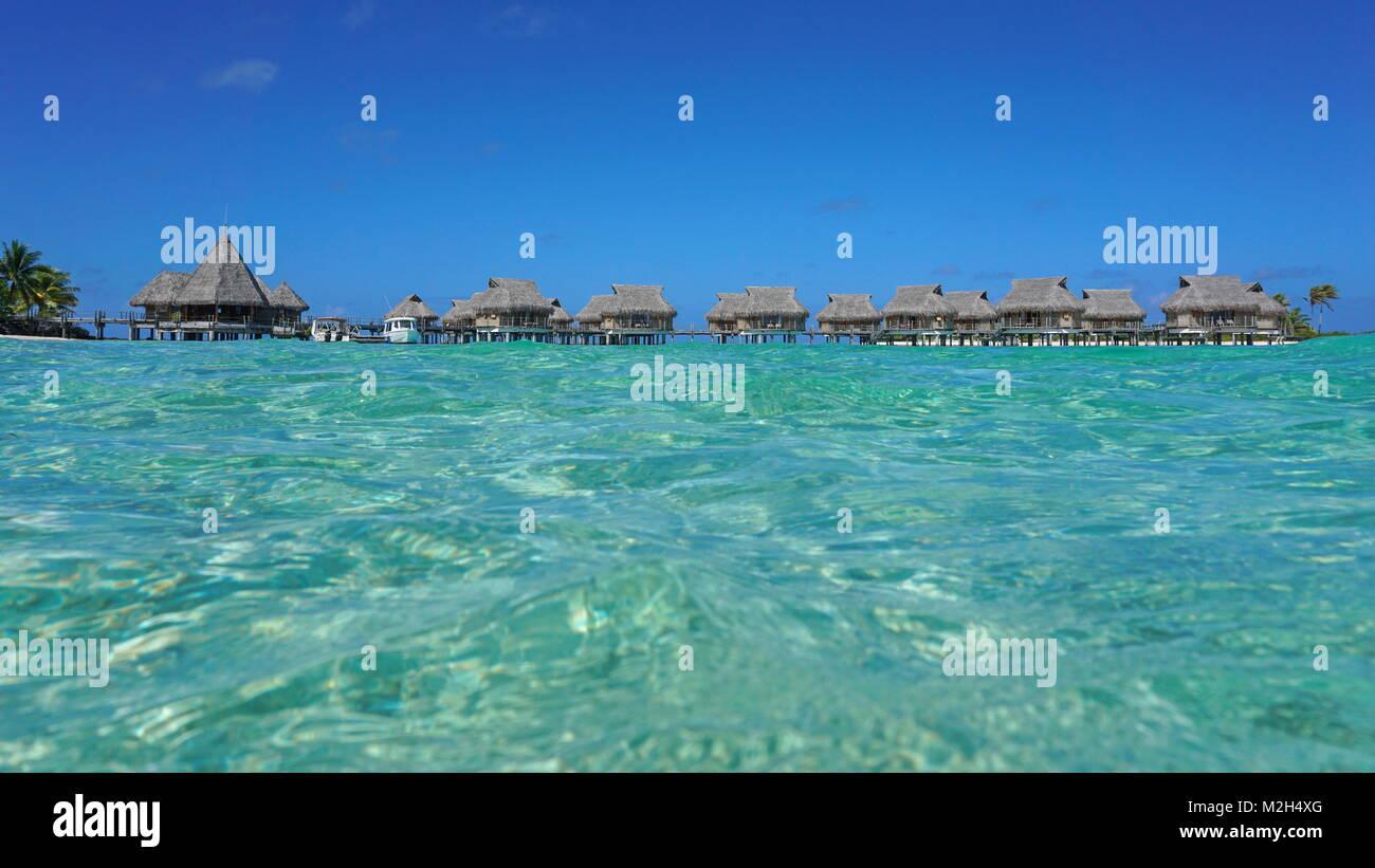 Tropical resort avec des bungalows au toit de chaume dans le lagon vu de surface de la mer, l'atoll de Tikehau, Photo Stock