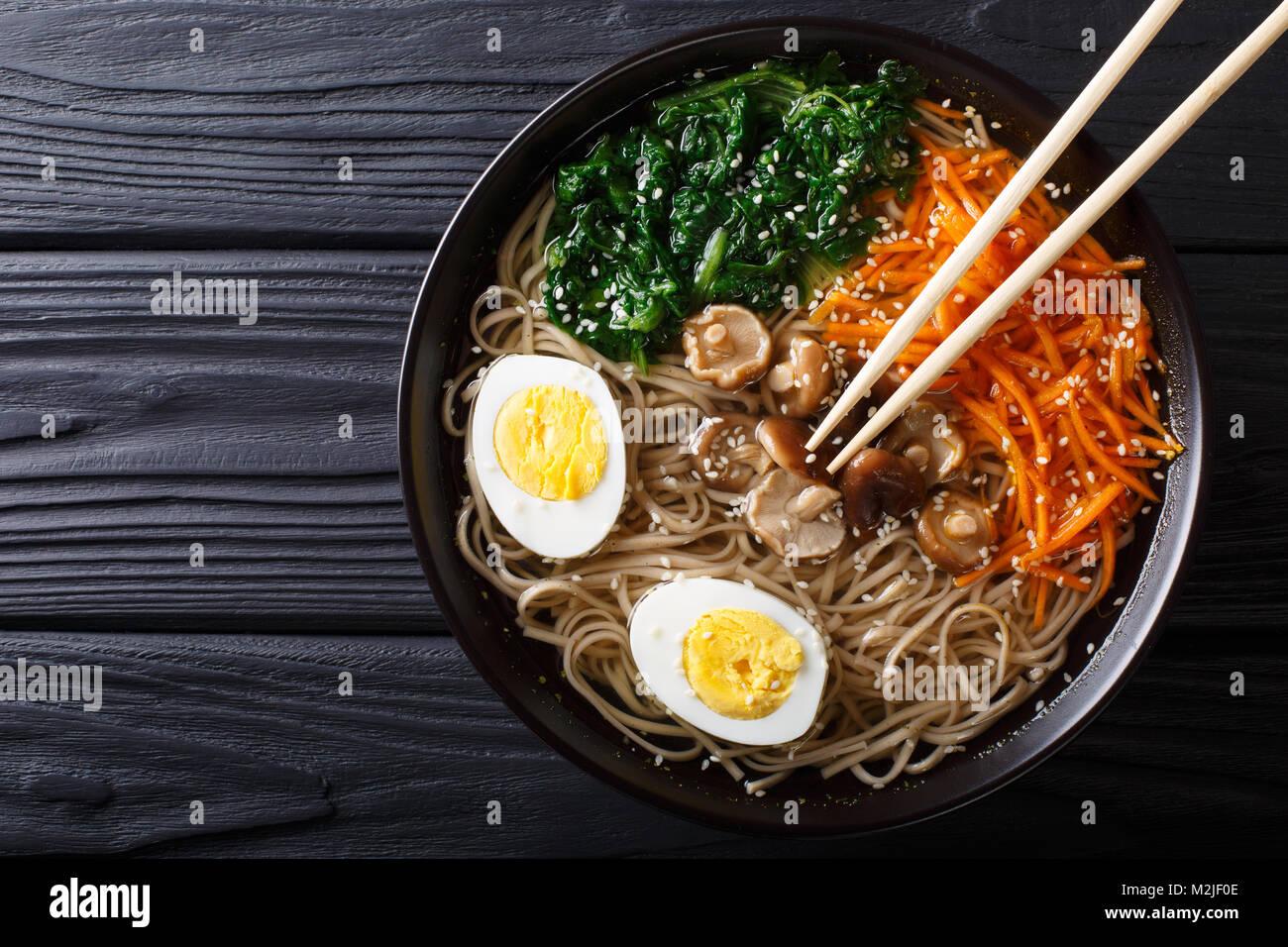 Soupe aux légumes Soba d'Asie, les champignons, l'oeuf et de graines de sésame close up dans un Photo Stock