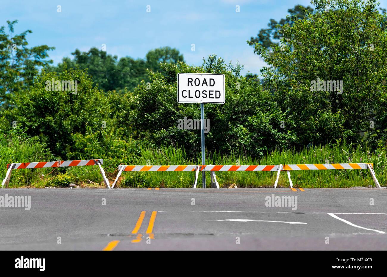 D'un coup horizontal road closed sign placé là où la route a pris fin. vert des arbres et arbustes Photo Stock