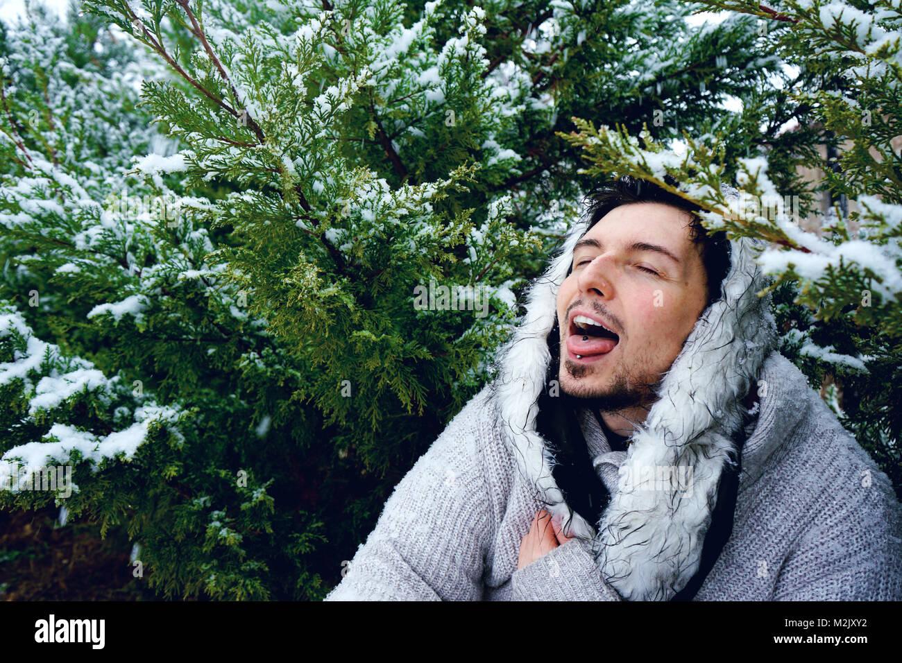 Jeune homme jouissant d'un jour de neige et d'hiver Banque D'Images