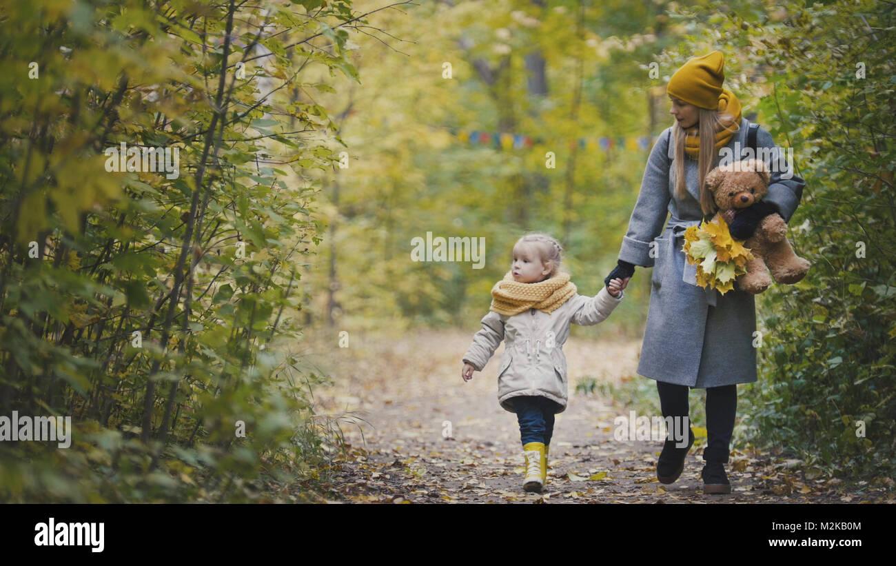Petite fille joyeuse avec sa maman et Teddy l'ours promenades dans autumn park Photo Stock