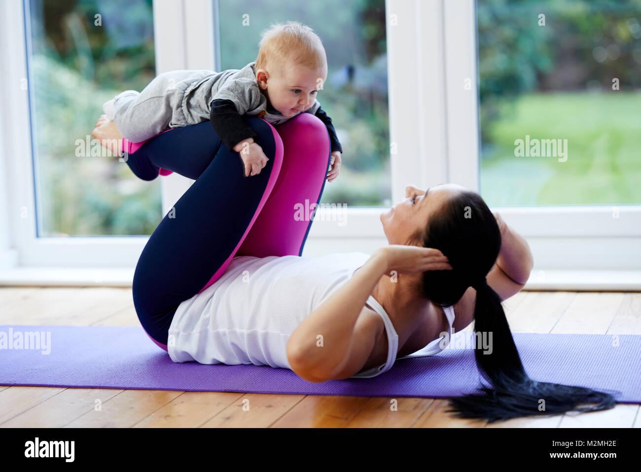 L'exercice de la mère avec son enfant Photo Stock