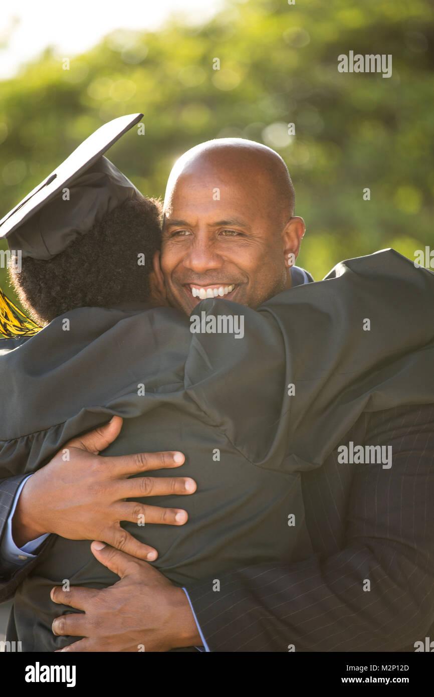 Père serrant son fils à son diplôme. Banque D'Images