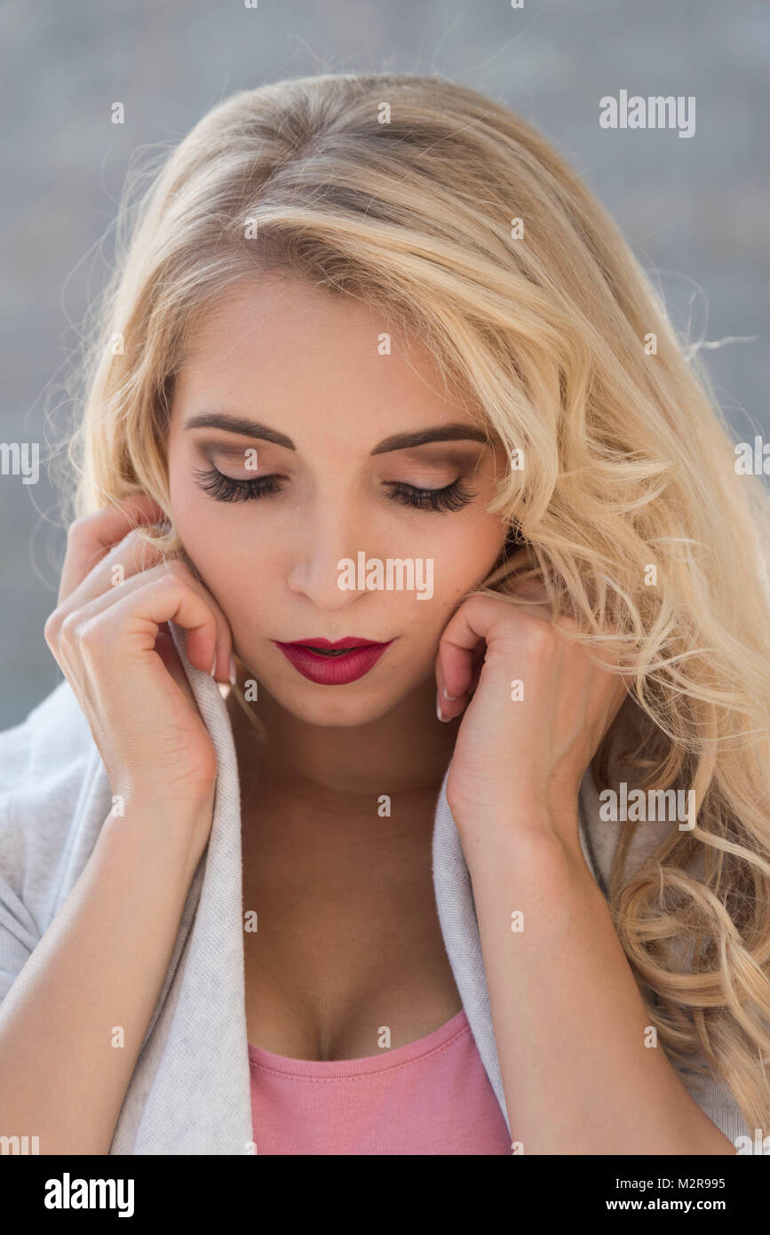 Jeune femme à l'extérieur, couvrir les oreilles baissés, look, portrait Photo Stock