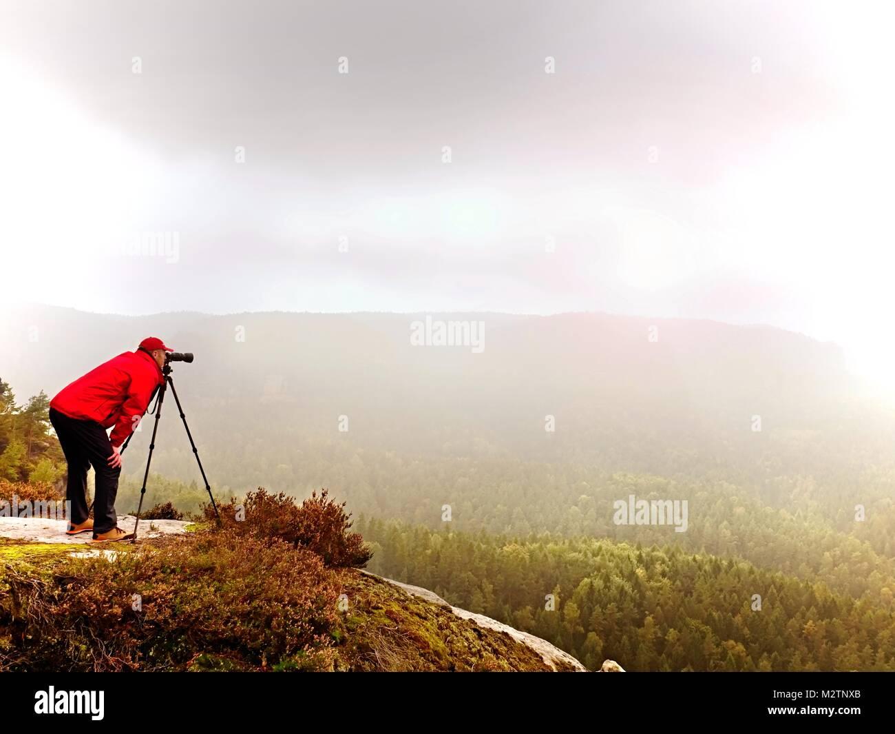 Photographe professionnel prise de vue. Artiste stay avec trépied sur sommet et prend des photos d'automne Photo Stock