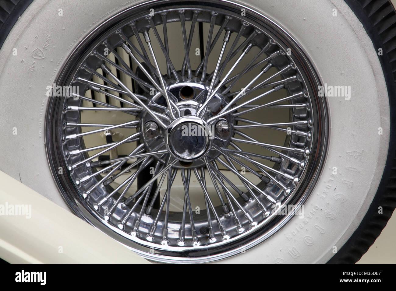 Vue rapprochée d'une paroi en acier blanc avec des pneus à rayons de roue fil Photo Stock