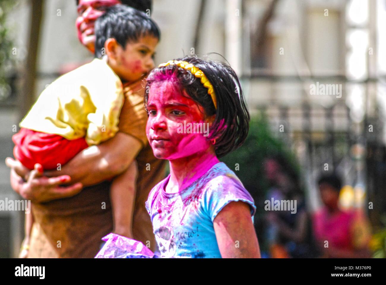 Une jeune fille est couverte dans la peinture en poudre lors de la fête de Holi à Hyderabad, Inde. Photo Stock