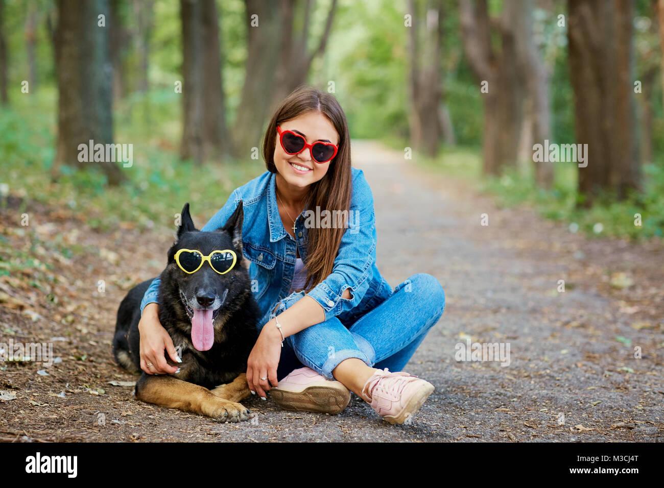 Jeune fille avec un chien en lunettes de soleil dans le parc. Berger allemand Photo Stock