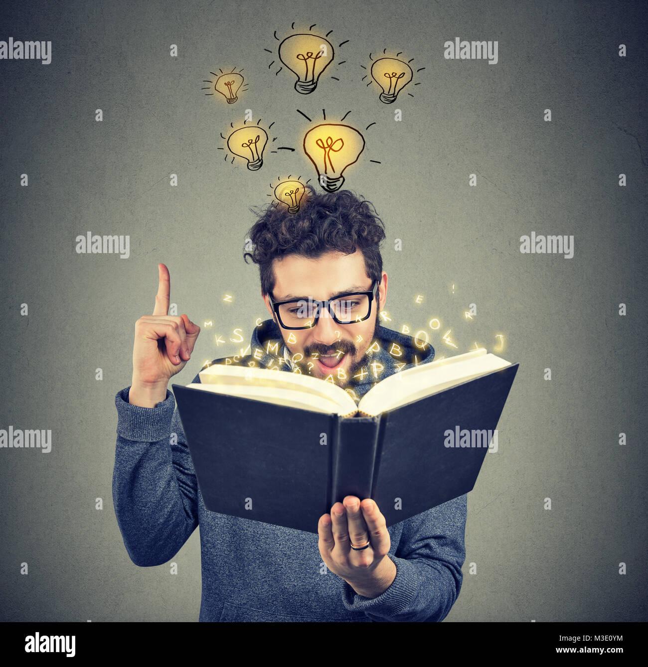 Jeune homme d'avoir la brillante idée de venir jusqu'à l'esprit lors de la lecture du livre Photo Stock