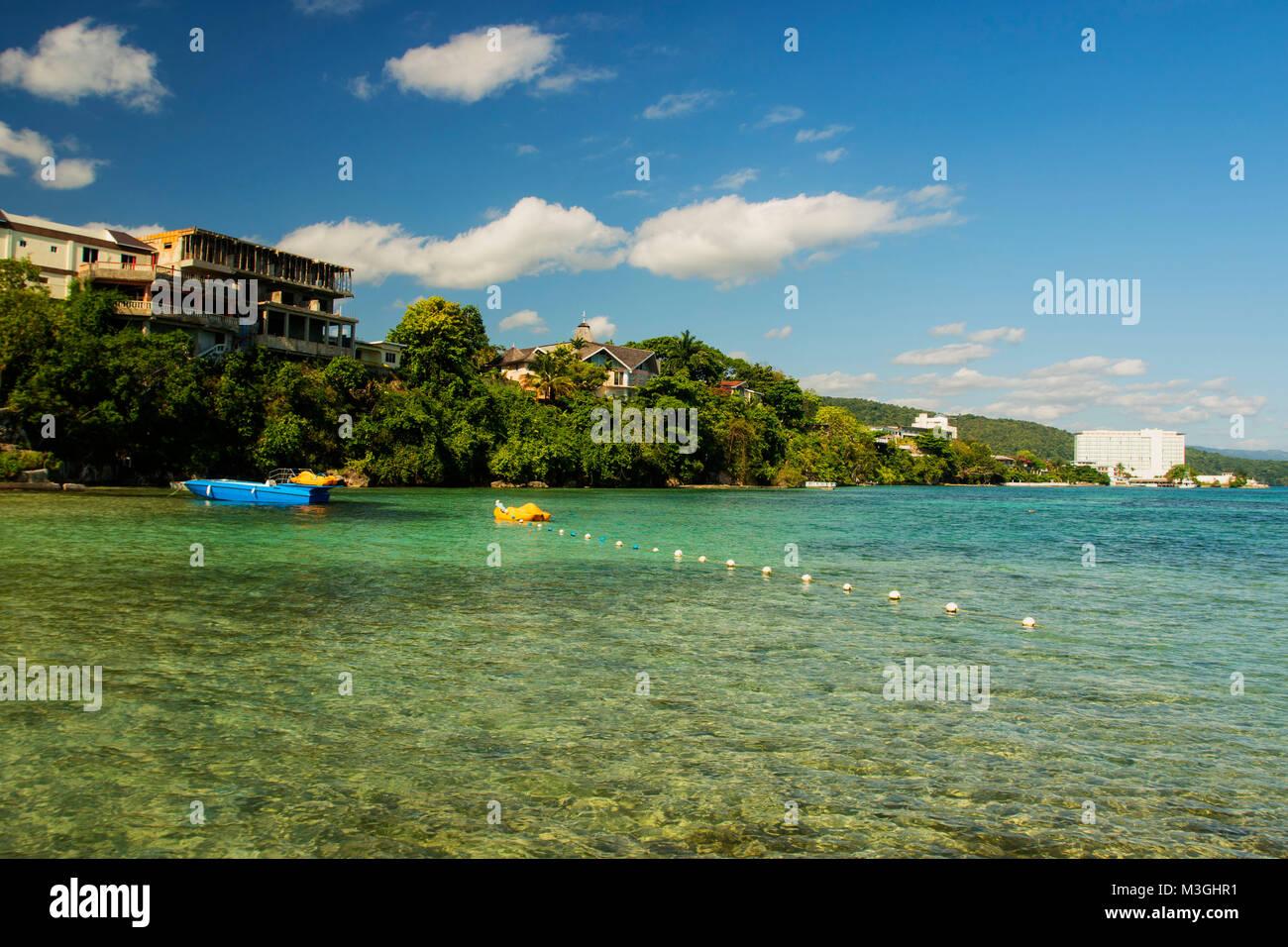 Mahogany Beach seascape avec bleu bateau sur une mer calme, Ocho Rios, Jamaïque, Antilles, Caraïbes Banque D'Images