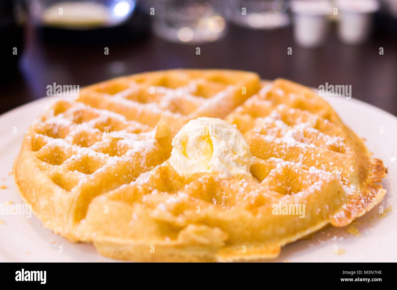 Le petit-déjeuner avec du beurre et de gaufres saupoudrées de sucre en poudre. Un premier repas traditionnel Photo Stock