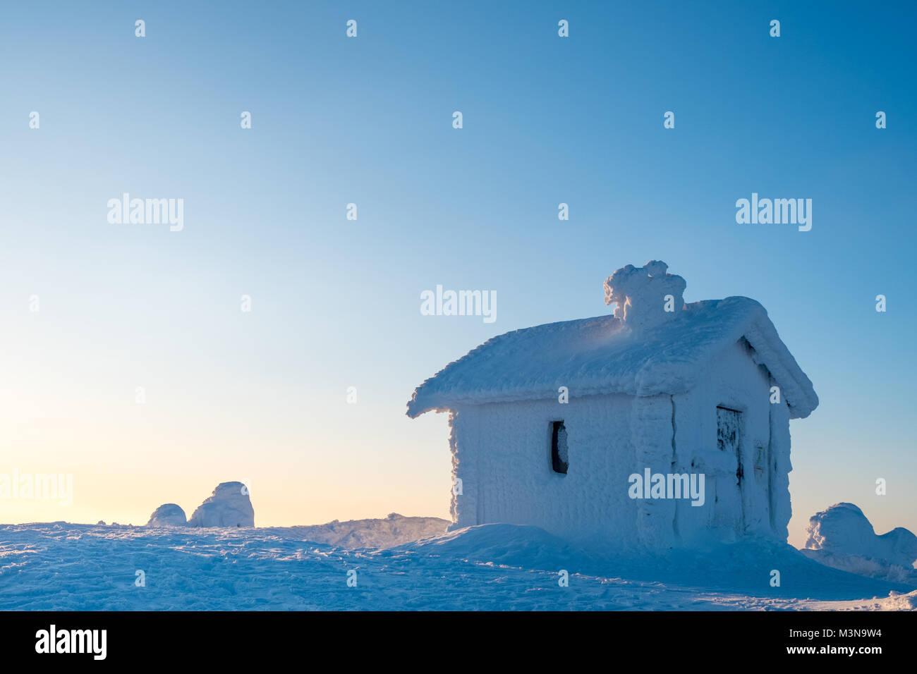 Une cabine incrustée de neige sur le sommet d'une colline en Finlande Photo Stock
