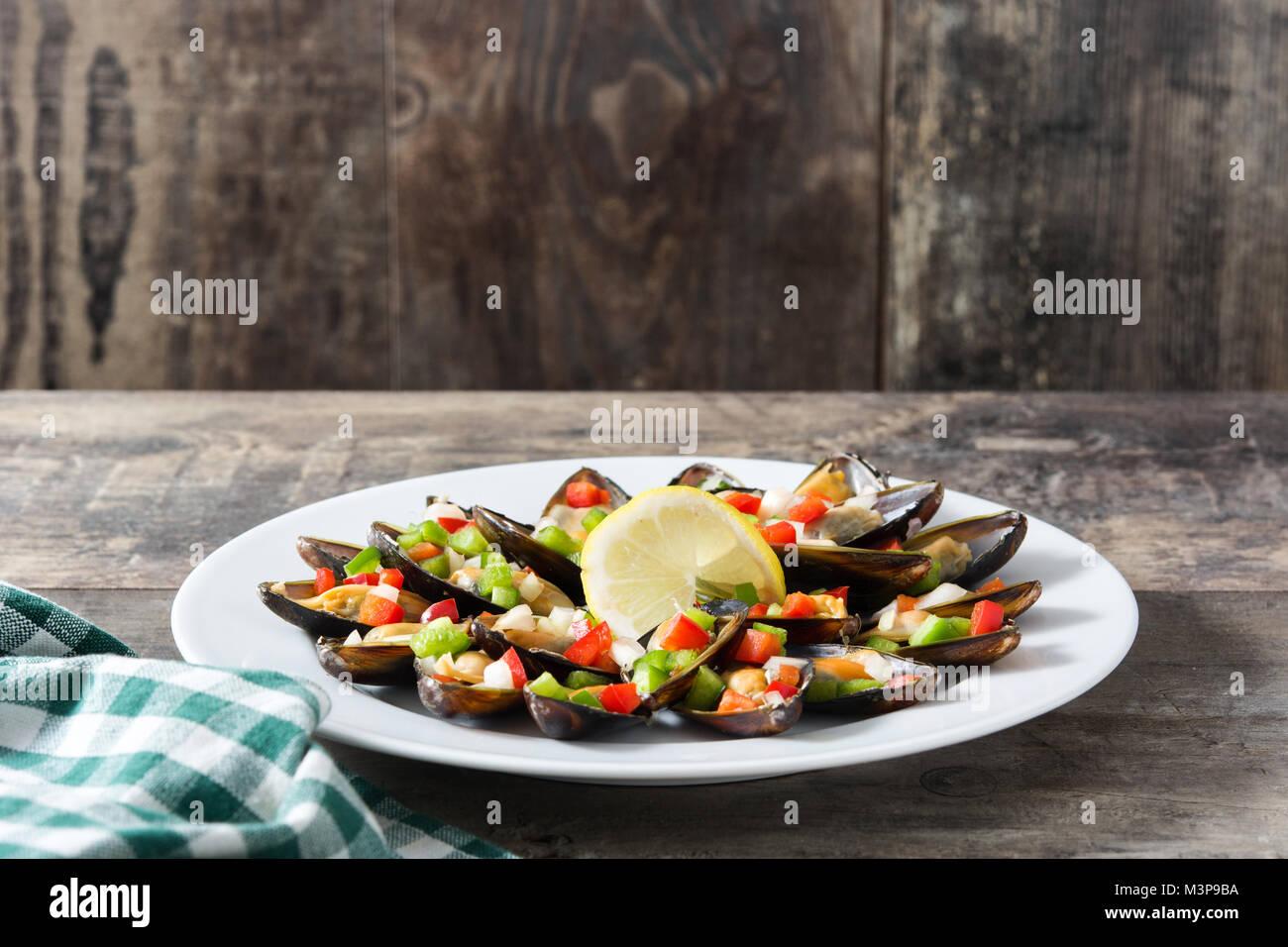 Les moules cuites à la vapeur avec des poivrons et oignons sur table en bois Banque D'Images