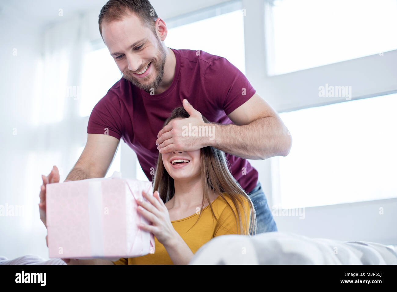 Cheerful man de faire un don à sa femme bien-aimée Photo Stock