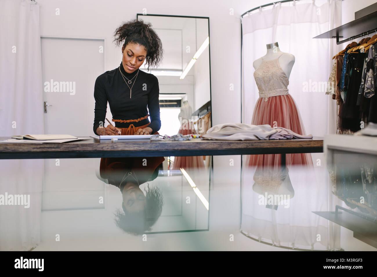 Designer de mode féminine design l'ébauche d'une assise à son tableau. Entrepreneur de mode Photo Stock