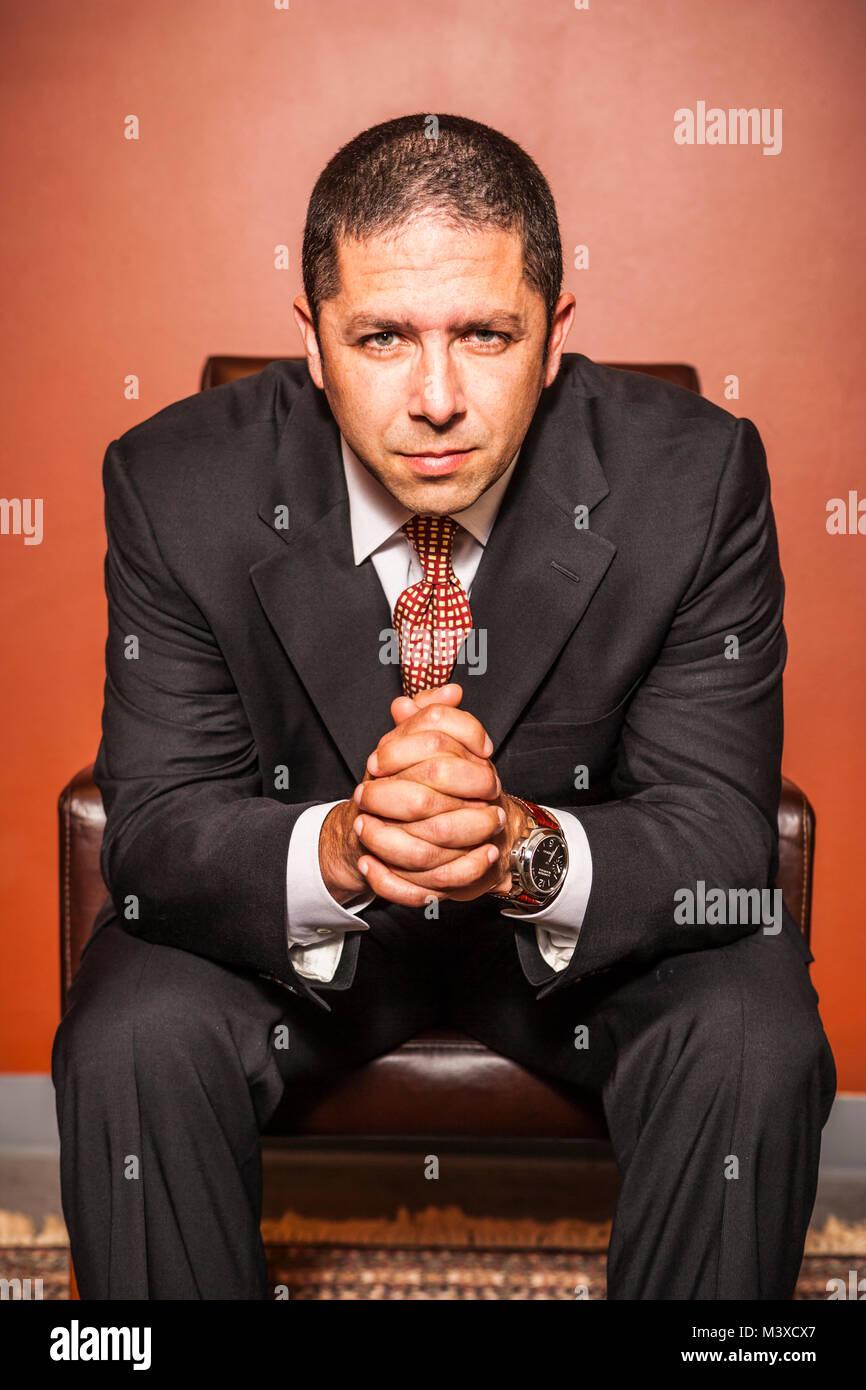Portrait d'un homme d'intense se penchant en avant sur sa chaise Photo Stock