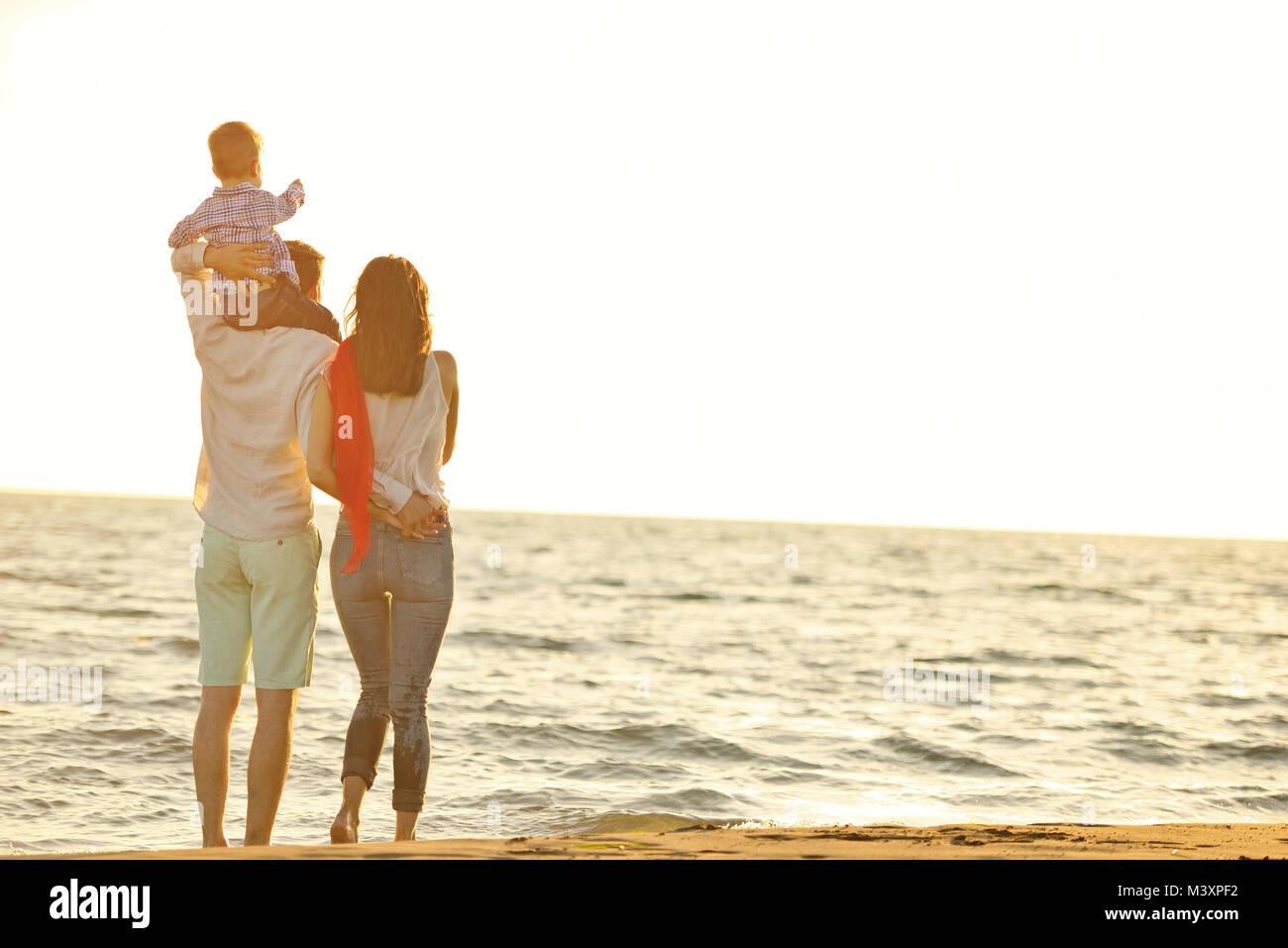 Portrait de famille heureuse et bébé profiter de coucher du soleil à l'été les loisirs Photo Stock