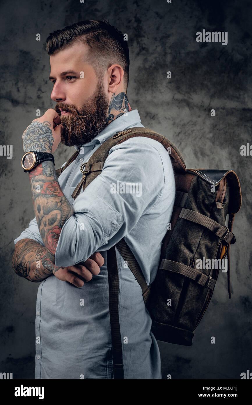 un homme avec des tatouages sur les bras et le cou avec sac à dos au