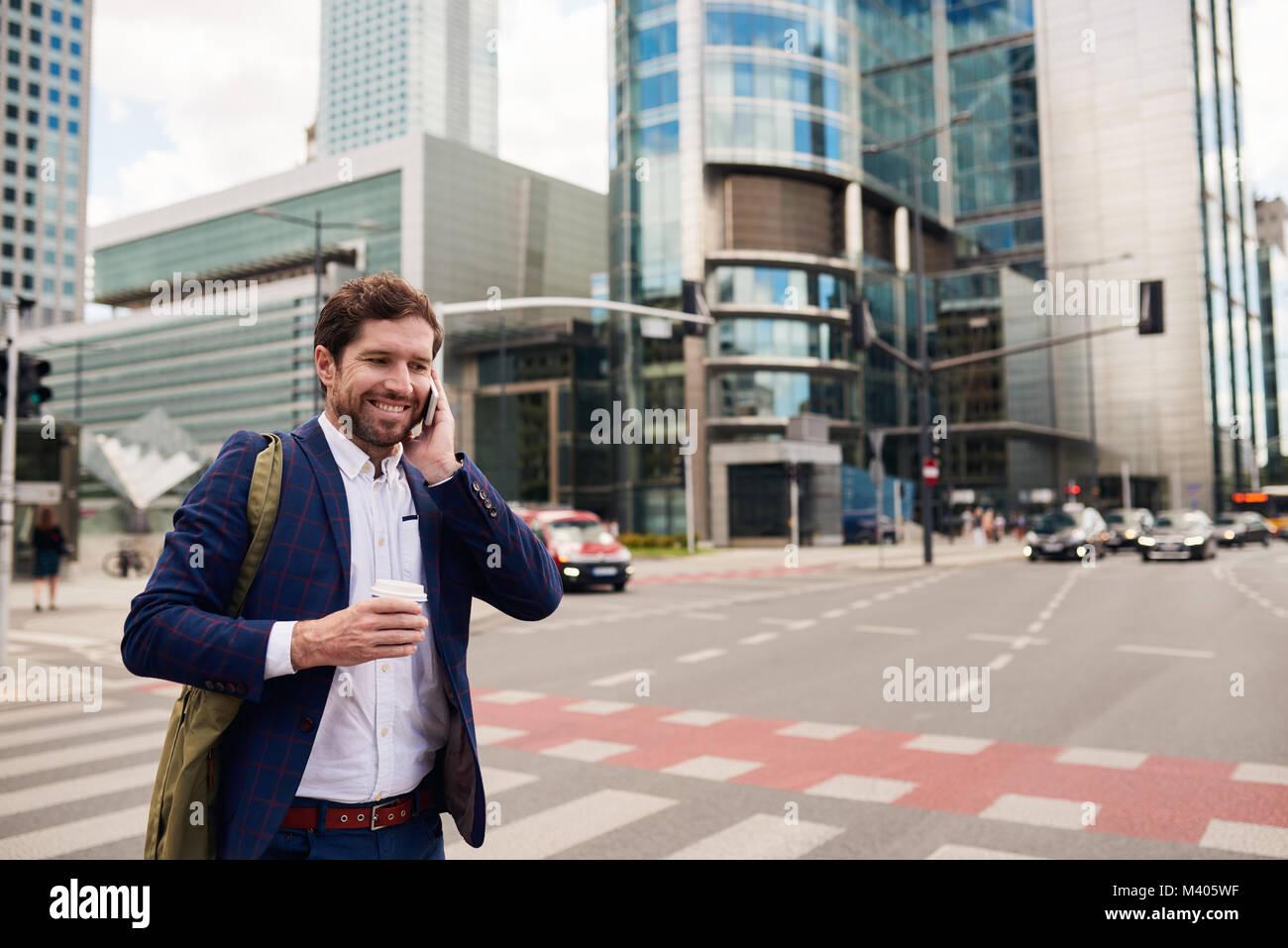 Smiling businessman walking pour travailler sur son trajet du matin Photo Stock